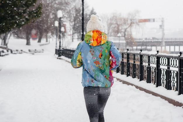 Uma linda jovem está correndo em um dia gelado e com neve. esportes, estilo de vida saudável