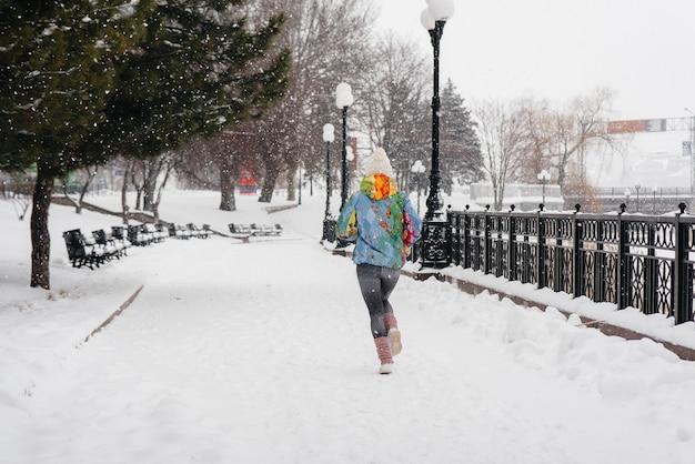 Uma linda jovem está correndo em um dia gelado e com neve. esportes, estilo de vida saudável.