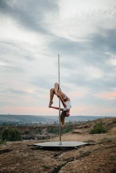 Uma linda jovem está envolvida em um poste durante o pôr do sol.
