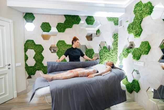 Uma linda jovem está fazendo um envoltório de corpo inteiro de procedimento de cosmetologia em um moderno salão de beleza. procedimentos de spa em um salão de beleza.