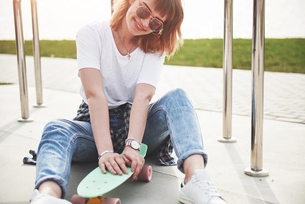 Uma linda jovem está se divertindo no parque e andando de skate.