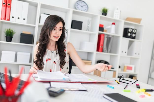 Uma linda jovem está sentado à mesa do escritório com documentos e uma caneta nas mãos e está negociando.
