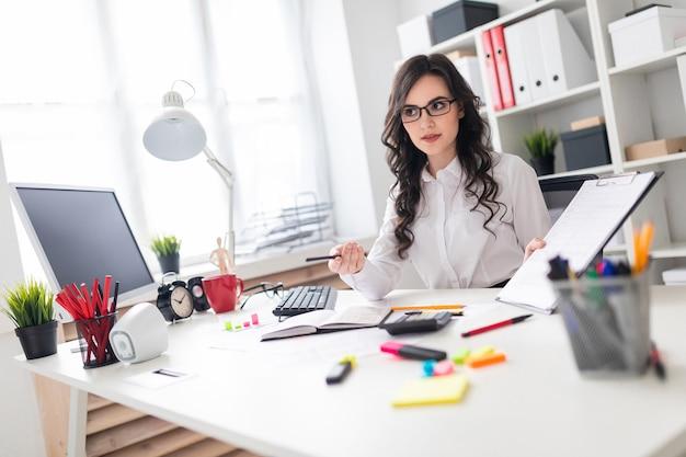 Uma linda jovem está sentado em uma mesa no escritório e apontando um lápis para as informações no documento.