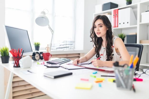 Uma linda jovem está sentado na mesa do escritório com documentos e uma caneta nas mãos dela e está negociando.