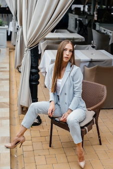Uma linda jovem está sentado na varanda de uma casa bonita. relaxamento.