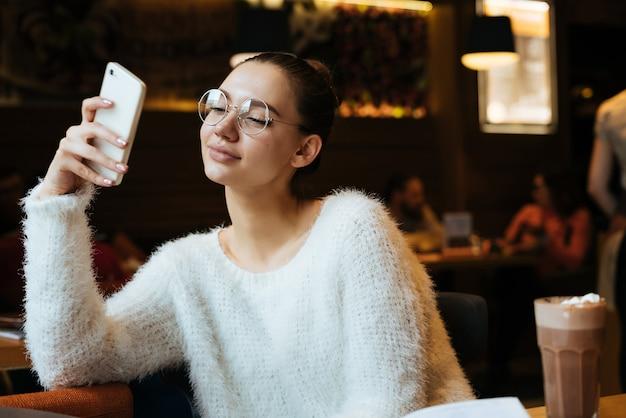 Uma linda jovem estudante de óculos sentada no café após o estudo, olhando para o smartphone