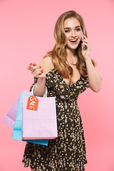 Uma linda jovem feliz posando isolada na parede rosa segurando sacolas de compras, falando por telefone celular