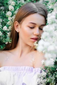 Uma linda jovem fica entre as árvores floridas. flores brancas. primavera.