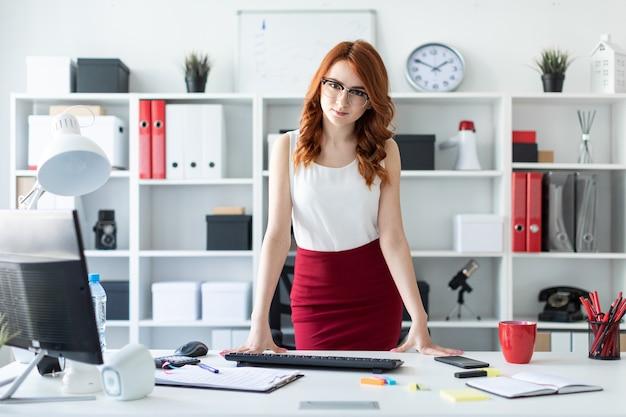 Uma linda jovem fica no escritório perto da mesa, colocando as mãos nela.