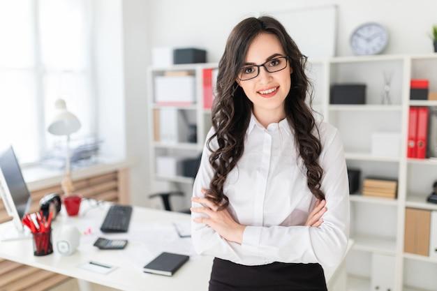 Uma linda jovem fica perto da mesa de escritório, as mãos entrelaçadas no peito