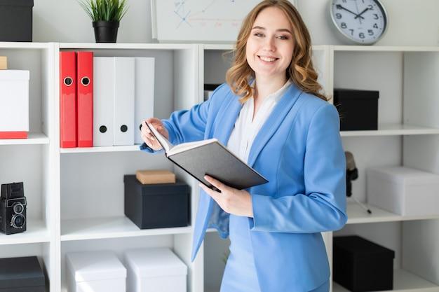 Uma linda jovem fica perto de um rack no escritório e detém um livro aberto nas mãos dela.