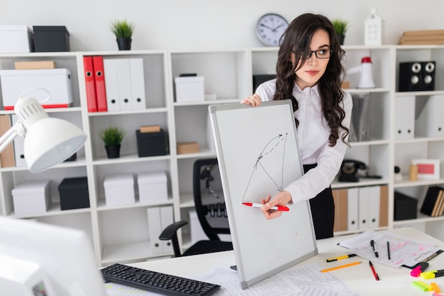 Uma linda jovem fica perto de uma mesa de escritório e desenha um marcador magnético no quadro magnético.