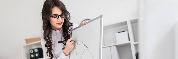 Uma linda jovem fica perto de uma mesa de escritório e desenha um marcador magnético no quadro magnético