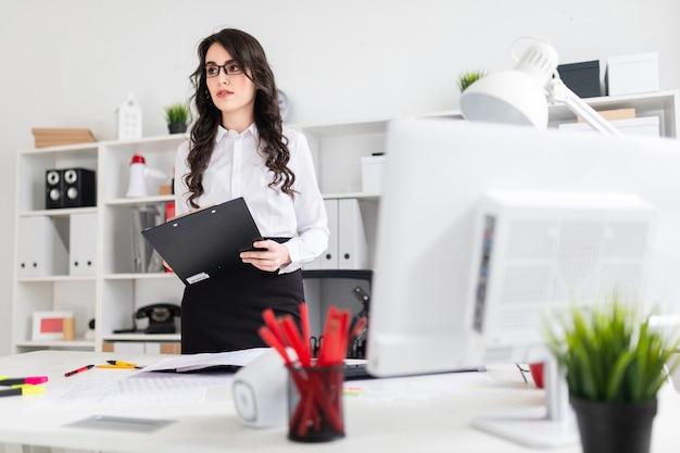 Uma linda jovem fica perto de uma mesa de escritório e segura uma folha para anotações.
