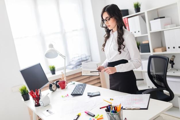 Uma linda jovem fica perto de uma mesa de escritório e tem um caderno e um lápis nas mãos dela.
