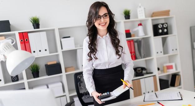 Uma linda jovem fica perto de uma mesa de escritório e tem uma caneta, caderno e calculadora nas mãos dela. a garota está liderando.