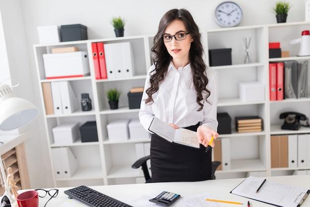 Uma linda jovem fica perto de uma mesa de escritório e tem uma caneta e um caderno nas mãos dela. a garota está negociando.