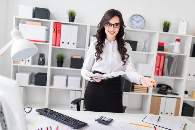 Uma linda jovem fica perto de uma mesa de escritório e tem uma caneta e um caderno nas mãos dela.