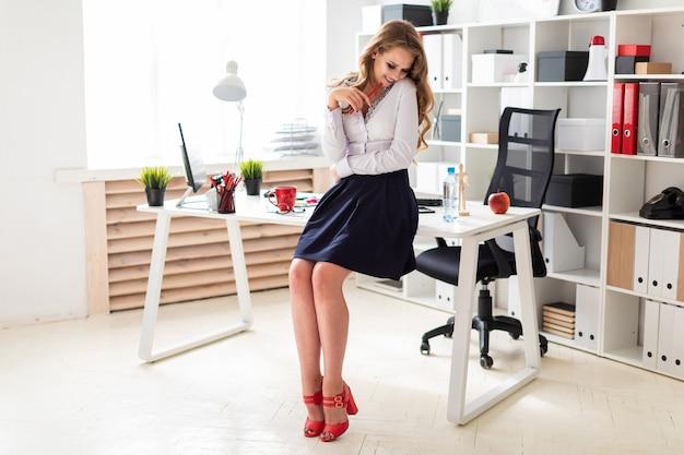 Uma linda jovem fica perto de uma mesa no escritório e tem um lápis vermelho nas mãos.