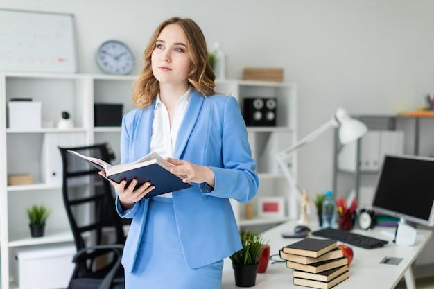 Uma linda jovem fica perto de uma mesa no escritório e tem um livro aberto nas mãos.