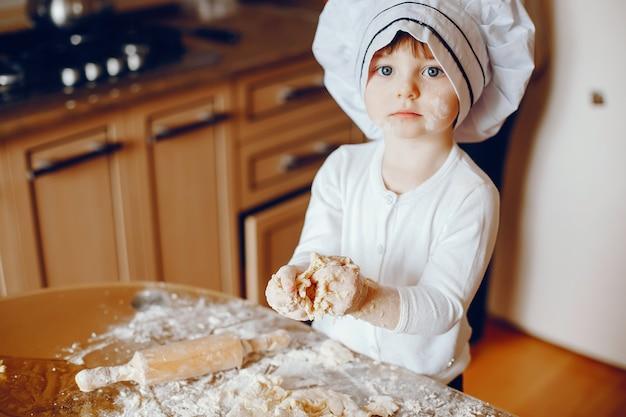 Uma linda jovem filhinha está cozinhando na cozinha em casa