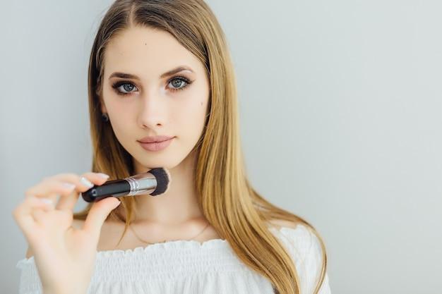 Uma linda jovem loira faz sua própria maquiagem em frente ao espelho