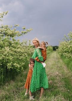 Uma linda jovem mãe brinca com dois filhos pequenos no jardim de primavera antes da chuva. o conceito de felicidade familiar