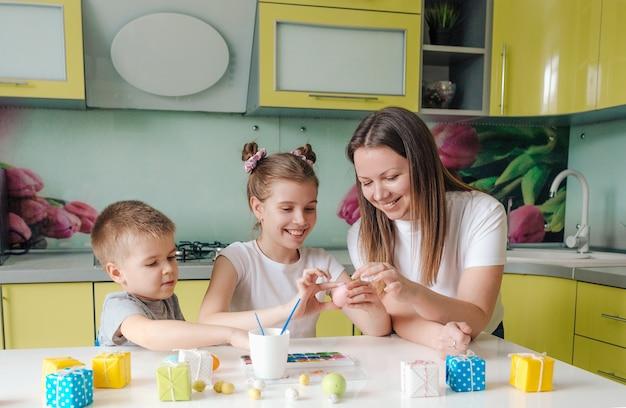 Uma linda jovem mãe com dois filhos decorou ovos de páscoa tradicionais com tinta brilhante, o conceito de uma família feliz se preparando para o feriado de páscoa