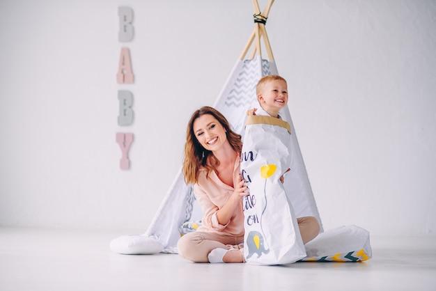 Uma linda jovem mãe e seu filho se divertindo na sala de luz. menino sorridente com doces sai de uma sacola ecológica de papel.