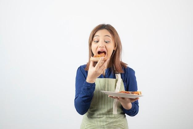 Uma linda jovem modelo de avental comendo pizza.