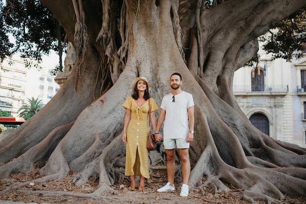 Uma linda jovem morena de chapéu e vestido amarelo com o namorado com barba sob uma velha árvore gigante de ficus macrophylla valenciana na espanha à noite. um casal de turistas em valência.