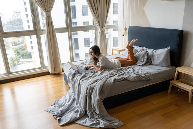Uma linda jovem morena está usando o laptop enquanto estava deitado em uma cama por uma janela panorâmica com uma bela vista de um andar alto