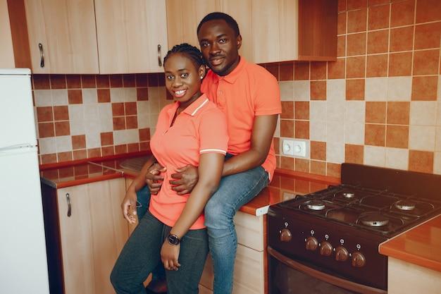 Uma linda jovem negra em uma camiseta rosa e jeans azul em pé em casa na cozinha