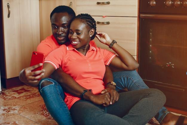 Uma linda jovem negra em uma camiseta rosa e jeans azul, sentado em casa na cozinha