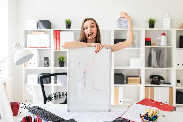 Uma linda jovem no escritório está de pé perto da mesa,