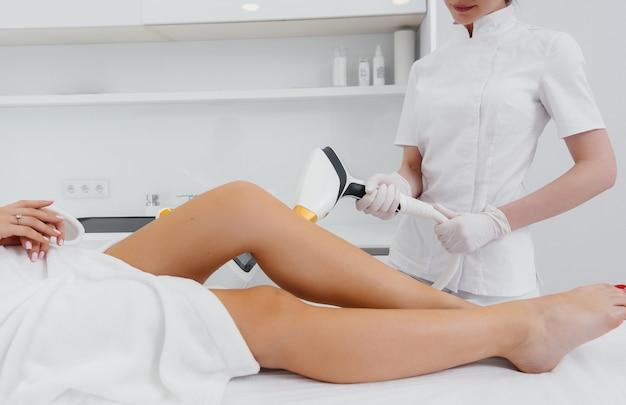 Uma linda jovem realizará um procedimento de depilação a laser com equipamentos modernos no close-up do salão do spa. salão de beleza. cuidado do corpo.