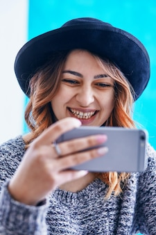 Uma linda jovem se comunicando por meio de um smartphone