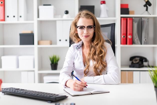 Uma linda jovem se senta em uma mesa no escritório com um bloco de notas e tem uma caneta na mão.