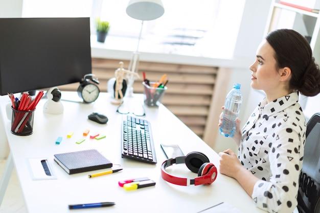Uma linda jovem se senta em uma mesa no escritório e detém uma garrafa de água nas mãos dela.