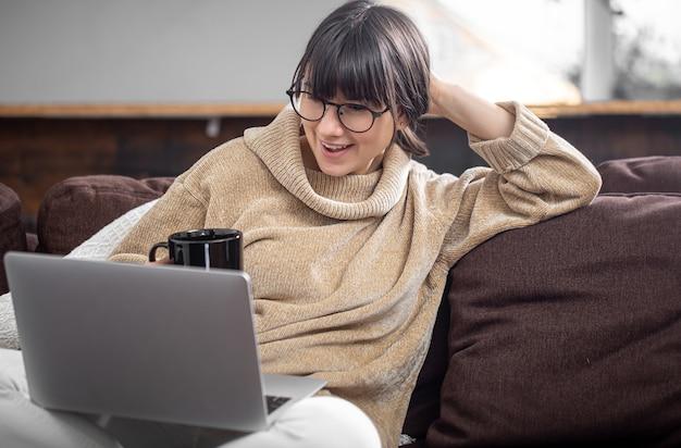 Uma linda jovem se senta no sofá em casa com um copo de bebida e olha alegremente para a tela do computador. o conceito de videocomunicação e comunicação à distância.