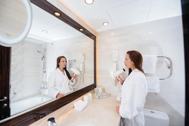 Uma linda jovem seca o cabelo com um secador de cabelo em um banheiro branco bonito. bom dia fresco no hotel.