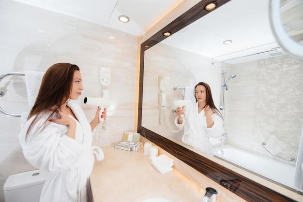 Uma linda jovem seca o cabelo com um secador de cabelo em um belo banheiro branco