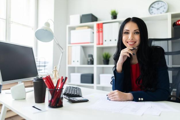 Uma linda jovem senta-se no escritório à mesa e tem um lápis na mão.