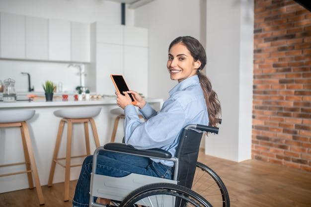 Uma linda jovem sentada na cozinha com um smartphone nas mãos