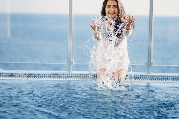 Uma linda jovem sentado num terraço de verão à beira da piscina
