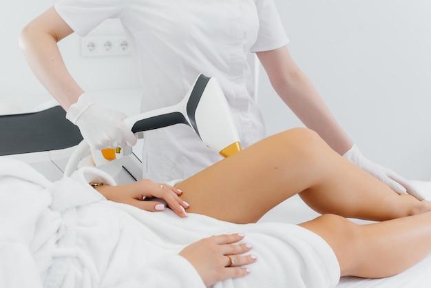 Uma linda jovem será submetida à depilação a laser com equipamentos modernos em um salão de beleza. salão de beleza. cuidados com o corpo.