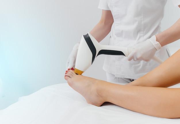 Uma linda jovem será submetida a depilação a laser com equipamentos modernos em um salão de spa. salão de beleza. cuidado do corpo.