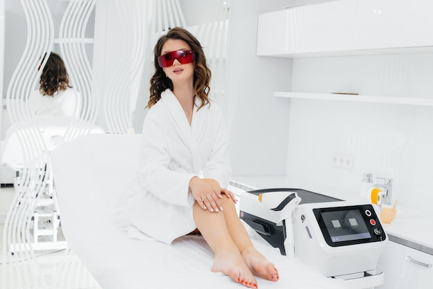 Uma linda jovem será submetida à depilação a laser com equipamentos modernos em um salão de spa. salão de beleza. cuidado do corpo.