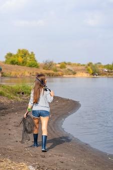 Uma linda jovem vai pescar. uma menina com uma vara de pescar e uma gaiola na mão está caminhando ao longo do lago