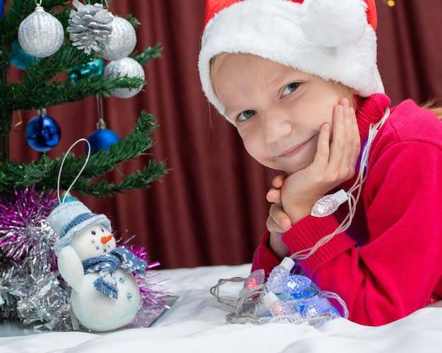 Uma linda loira caucasiana com um suéter vermelho e um boné de natal olha para você com ar sonhador, a garota está deitada ao lado de uma árvore de natal decorada, um boneco de neve de brinquedo. conceito de feliz natal e ano novo
